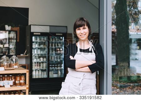Portrait Of Owner Of Sustainable Small Local Business. Shopkeeper Of Zero Waste Shop Standing On Int