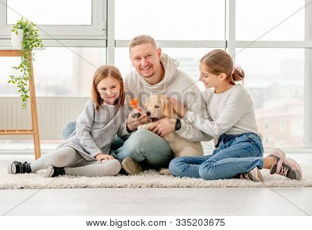 Happy family and golden retriever puppy sitting together indoors