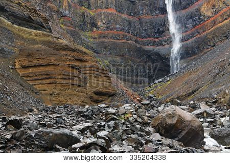 Hengifoss Canyon with the Hengifoss Waterfall, the third highest waterfall in Iceland is surrounded by basaltic strata with red layers of clay between the basaltic layers