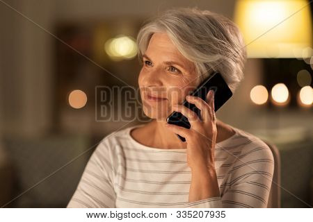 technology, communication and people concept - happy senior woman calling on smartphone at home in evening