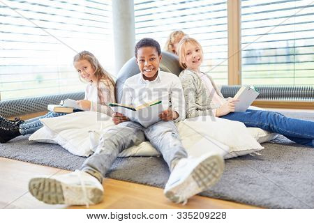 Group of kids of elementary school while reading relaxed in free time