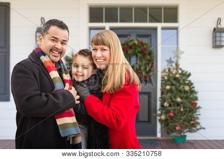 Young Mixed Family On Front Porch of House with Christmas Decorations.