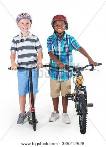 Two smiling diverse schoolboys isolated on a white background. Full length photo of the boys On their way to school riding a bike and a scooter. Education concept photo