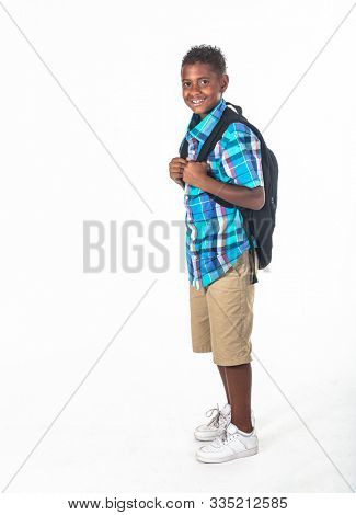 Smiling African American school boy on white background. Wearing a backpack and a plaid shirt and ready to go to school. side view