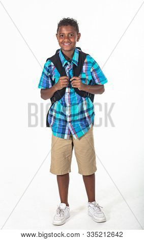 Smiling African American school boy isolated on white background. Wearing a backpack and a plaid shirt and ready to go to school. Front view