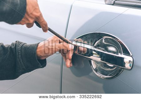 Auto Thief In Black Balaclava Trying To Break Into Car With Screwdriver. Car Thief, Car Theft