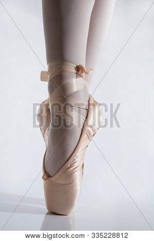 Close-up Of Feet With Pink Satin Pointe Shoes By A Classic Ballerina On Tiptoe