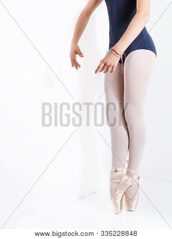 Detail Of Legs And Feet With Pink Satin Pointe Shoes By A Classic Ballerina On Tiptoe