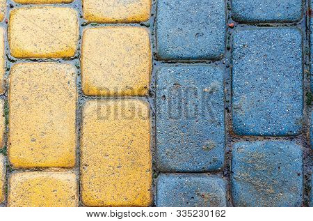 Yellow And Blue Cobbles Of Pavement Texture. Stone Masonry Floor Covering Close Up. Top View Of Vert