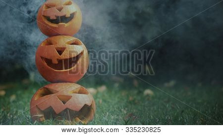 Scary Carved Halloween Pumpkins Symbolize Mistery And Horror. Three Spooky Pumpkins Lined Up In A Py