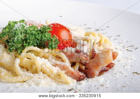 Typical Spaghetti Alla Carbonara  With Raw Egg And Bacon. Served On A White Plate With Grated Pecori