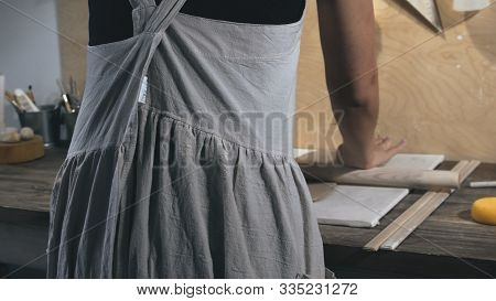 Master Female Potter Wearing An Apron Preparing And Rolling Clay With A Rollingpin. Female Hands Rol