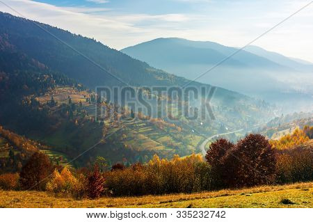 Carpathian Rural Area In Autumn. Wonderful Landscape In Mountains On A Hazy Day. Village In The Dist