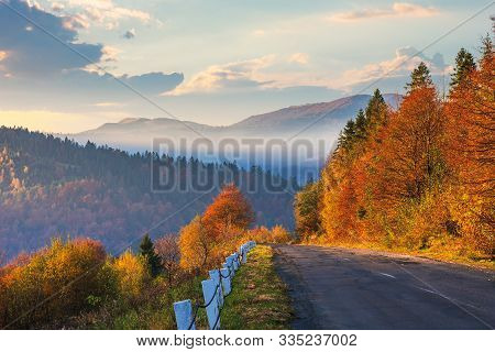 Asphalt Road Through Forest. Beautiful Mountain Landscape. Trees In Fall Foliage. Foggy Weather At S