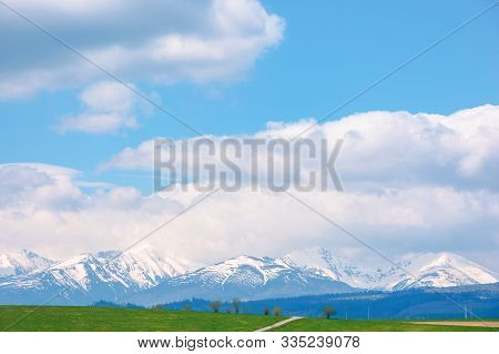 Snow Capped Western High Tatras Ridge In Springtime. Beautiful Sunny Weather With Clouds On A Blue S