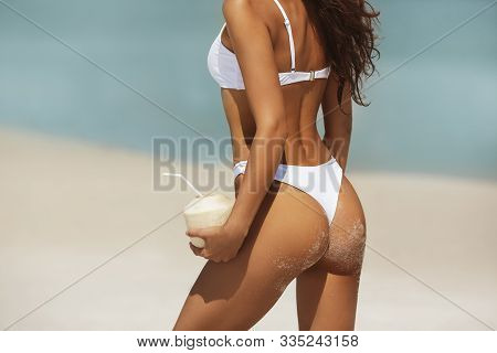 Young Woman In White Bikini On The Tropical Beach With Coconut. Attractive Tanned Brunette Girl Hold