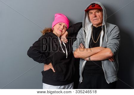 Horizontal Photo Of Nonchalant Pensioners Staying Near Gray Background