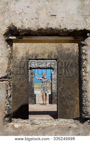 Caucasian Woman Is Standing In Doorway Of Historic Building At Bonaire