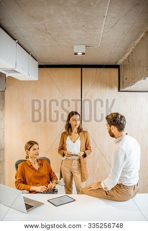 Office Employees Having Some Informal Conversation At The Workplace In The Office