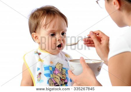 Mother Feeds Baby Girl With Spoon