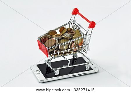 Shopping Cart Full Of Coins On Mobile Phone - Concept Of E-commerce And Mobile Payment