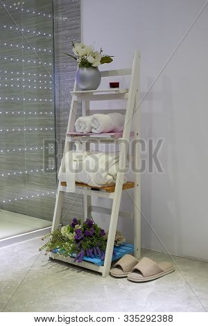 Modern Wooden Shelf Ladder In The Bathroom. Bathroom With Slippers, White Towels And A Bathrobe. Des