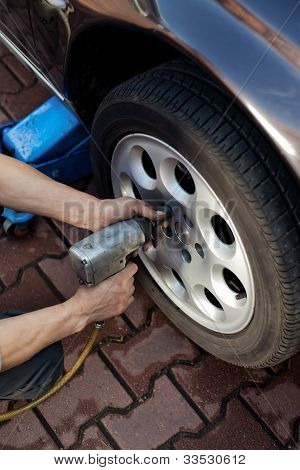 Car Mechanic Changing Wheel