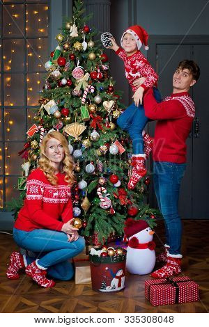 Christmas Family Portrait In Red Traditional Sweaters In Home Holiday Living Room, Parents And Child
