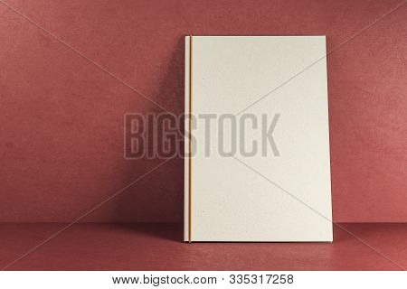 Empty White Hardcover Text Book On Red Background. Publish And Mock Up Concept. 3d Rendering