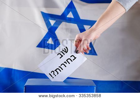 Israeli Woman Votes On Election Day. Hebrew Text Elections Again On Voting Paper Over Israel Flag Ba