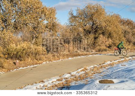 Winter commuting on a bike trail - Poudre River Trail in northern Colorado with praire dog colony covered by snow