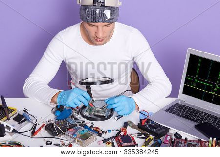 Horizontal Picture Of Young Professional Radiotrician Testifying Disk Driver With Multimeter, Using