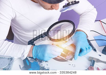 Photo Of Radioman With Soldering Iron Doing Repairs Work Through Magnifying Glass, Wearing White Swe
