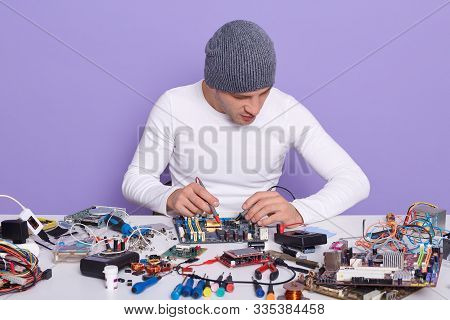 Electronic Engineer Measuring Voltage Of Electronic Curcuit Board With Help Of Multimeter, Working A