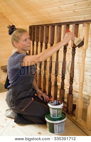 Beautiful Young Woman Painstakingly Paints The Balusters Of The Railing. Construction And Repair.