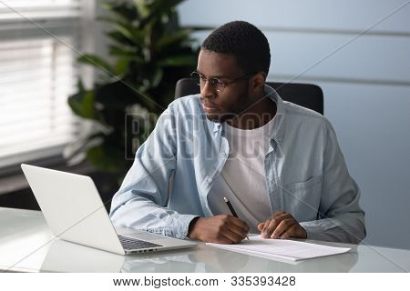 Focused African American Man Make Notes Watching Webinar On Laptop