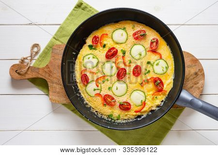 Omelette With Zucchini, Lamb's Lettuce, Tomatoes And Red Pepper In A Pan. Frittata - Italian Omelet.