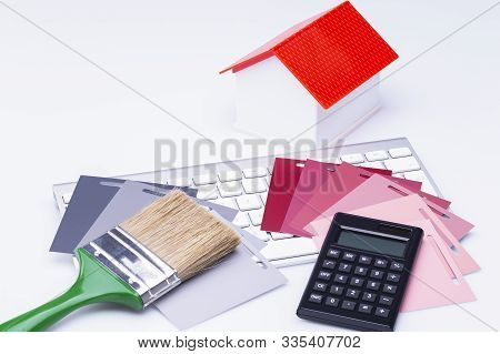 The Photo Shows A Model House With Various Color Cards A Brush And A Calculator On A Keyboard