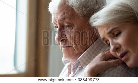 Worried Middle Aged Woman Embracing Upset Old Man.