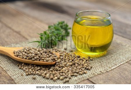 Cbd Hemp Oil In A Glass Bottle.hemp Seeds In A Wooden Spoon  The Hemp Leaf Is Placed On The Table. T