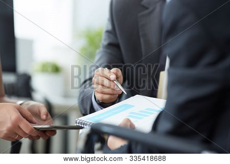 Businessman And Woman Discussing On Stockmarket Charts In Office. Men In A Suit Hold A Clipboard Wit