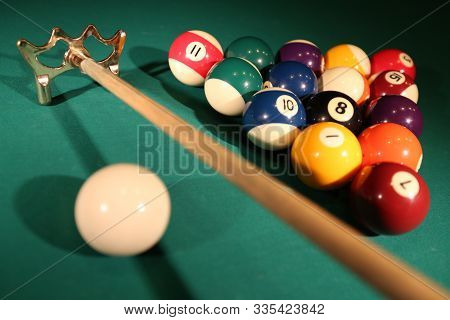 Sports Game Of Billiards On A Green Cloth. Multi-colored Billiard Balls In The Shape Of A Triangle W