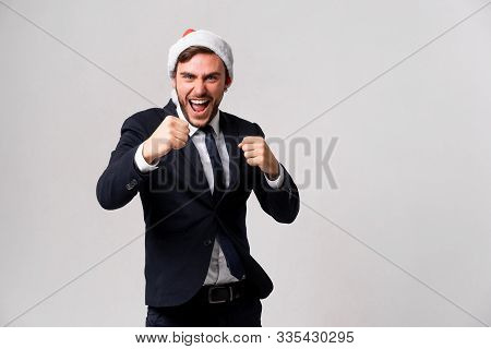 Young Handsome Caucasian Guy In Business Suit And Santa Hats On White Background Studio Screams And