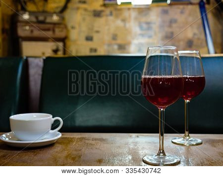 Cup Of Coffee And Two Wine Glasses On Table In Bar Cafe