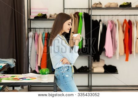 Running Fashion Business. Aspiring Couturier Girl Having Coffee Standing In Own Dressmaking Studio.