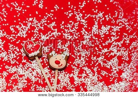 Christmas Sweets On A Red Background: Gingerbreads In The Shape Of Mittens And Deer. Festive Mood, L