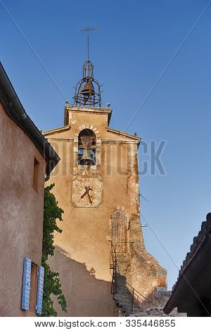 The Belltower Of The Main Church In Roussillon Has A Clock And An Unusual Entry Door Near The Top Of