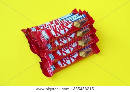 Kit Kat Chocolate Bars In Red Wrapping Lies On Yellow Background. Kit Kat Created By Rowntrees Of Yo