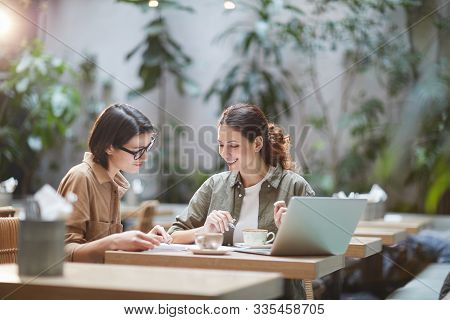 Portrait Of Two Cheerful Young Omen Enjoying Work In Beautiful Outdoor Cafe, Copy Space