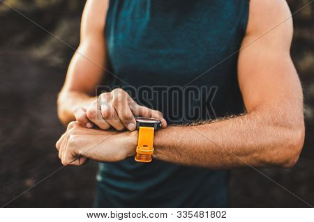 Young Athletic Man Using Fitness Tracker Or Smart Watch Before Run Training Outdoors. Close-up Photo